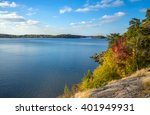 Stock photo autumnal lake shore with forest under sky trees on rock coast of rippling lake in autumn sunny day 401949931