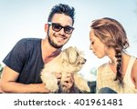 Stock photo portrait of young happy couple playing with dog in a park 401961481