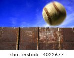 Baseball flying through the air with clouds sky and fence in background - stock photo
