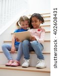 two girls sitting on staircase... | Shutterstock . vector #402608431