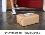 Small photo of Close Up Of Man Collecting Parcel Delivery Outside Door