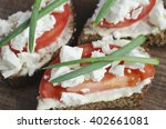 Small photo of slices of rye bread with sire feta, tomato and onion.
