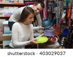 Stock photo portrait of young couple purchasing pet bowls in petshop 403029037