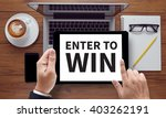 Small photo of ENTER TO WIN , on the tablet pc screen held by businessman hands - online, top view