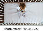 top view of baby sitting in crib | Shutterstock . vector #403318927