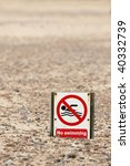 humorous no swimming sign on a pebbled beach - stock photo