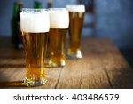 three glasses of light beer on... | Shutterstock . vector #403486579