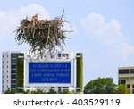 Small photo of FORT MYERS BEACH, USA - MAY 11, 2015: An osprey sitting in its aerie on top of a sign for nature protection, in the back some highrise residential buildings.