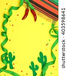 Small photo of A green ribbon border winds in and out of frame and is decorated with a serape blanket, red chili peppers, felt cutout cactus shapes and confetti on a yellow background for Cinco de Mayo in May