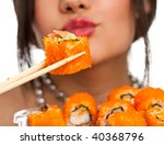 Beautiful young woman eating sushi california roll . Shallow depth of field, focus is on the sushi. isolated, studio. - stock photo