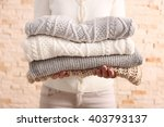 woman holding knitted clothes ... | Shutterstock . vector #403793137