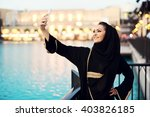 arabian woman taking selfie. | Shutterstock . vector #403826185