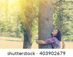 Young Woman Hugging A Tree In...