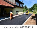 Small photo of Team of Workers making and constructing asphalt road construction with steamroller. The top layer of asphalt road on a private residence house driveway