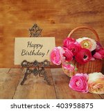 Small photo of pink flowers in the basket next to card with phrase: happy birthday, on wooden table.
