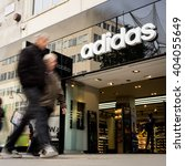 Small photo of LONDON, UK - 23 NOVEMBER 2011: Blurred shoppers walking past the shop front to the Adidas store, a sports retailer, on London's Oxford Street.