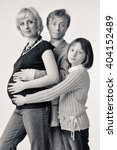 Small photo of All together cuddling. Pregnant woman, man and their daughter.