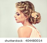Small photo of Beautiful model girl with elegant hairstyle and rose flowers in a plait . Woman with fashion wedding hair.