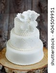 Small photo of Three layered wedding cake covered with white fondant, decorated with beads and hand-made flower on top