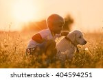 Stock photo young child boy training golden retriever puppy dog looking right 404594251