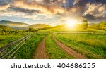 winding road near the wooden fence through the agricultural grassy meadow with lonely tree on hillside in high mountains at sunset - stock photo