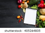 Small photo of Healthy organic vegetables with recipe notebook or shopping list and spices