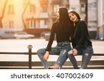Two Young Adult Women Sitting...