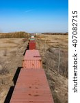 Overhead view of containers on a railway track leading Into the horizon - stock photo