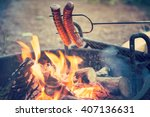 preparing sausages on camp fire | Shutterstock . vector #407136631