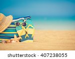 flip flops and bag on sandy... | Shutterstock . vector #407238055