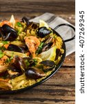 Small photo of Typical Spanish seafood paella in traditional rustic pan