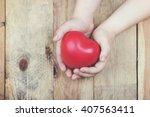 heart in a hands of a child | Shutterstock . vector #407563411