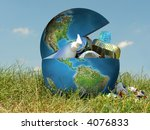 Earth globe in grass filled with assorted trash - concept representing environmental contamination of our planet by people and industry - stock photo