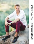 Small photo of Handsome man sitting on rock, outdoor. Boy leaning on his knees and holding his hands together. Man wearing white shirt, claret trousers and watch. Looking at camera and smiling. Full body