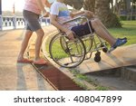 Small photo of Mother helping her son on wheelchair up the ramp in the park with sunset in background, warm filter