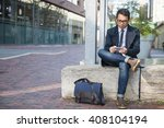 Stock photo young serious asian business man looking at mobile phone sitting outside on city street with copy 408104194