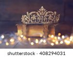 Small photo of low key image of beautiful diamond queen crown on old book. vintage filtered with glitter overlay. selective focus. medieval period concept