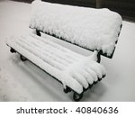 Snow covered bench in a winter day - stock photo