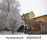 Snow covered house and trees in a winter day - stock photo