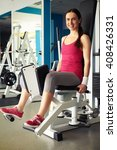 Small photo of Young Caucasian smiling woman is working out on hip abductor machine in gym