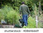 a man pushing a wheelbarrow on... | Shutterstock . vector #408646669