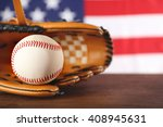 Small photo of Baseball in glove in front of American state flag