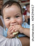 Small photo of 9 month old mixed race Asian Caucasian boy cheekily holds a piece of apple while sitting in his mother's arms