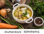 Fresh fish soup with ingredients and spices for cooking. Wooden background