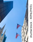 New York, USA - 4 September 2014: View looking up at a blue sky above 5th Avenue in Manhattan with flags of the United States and the spires of St Patricks Cathedral clearly seen.
