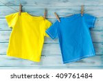 Stock photo two bright baby t shirts hanging on a clothesline on a blue wooden background 409761484