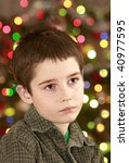 young boy face on the christmas tree with colorful lights background, expecting of gifts - stock photo