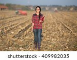 Young Woman Farmer Walking On...