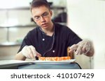 male cooks preparing sushi in... | Shutterstock . vector #410107429