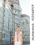 Small photo of An amble around awe-inspiring Duomo in Florence, Italy. Smiling young woman tourist standing in the front of Duomo